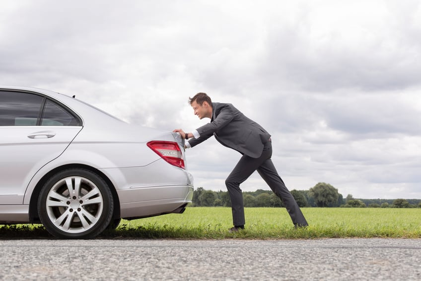 Full length side view of young businessman pushing broken down car on road